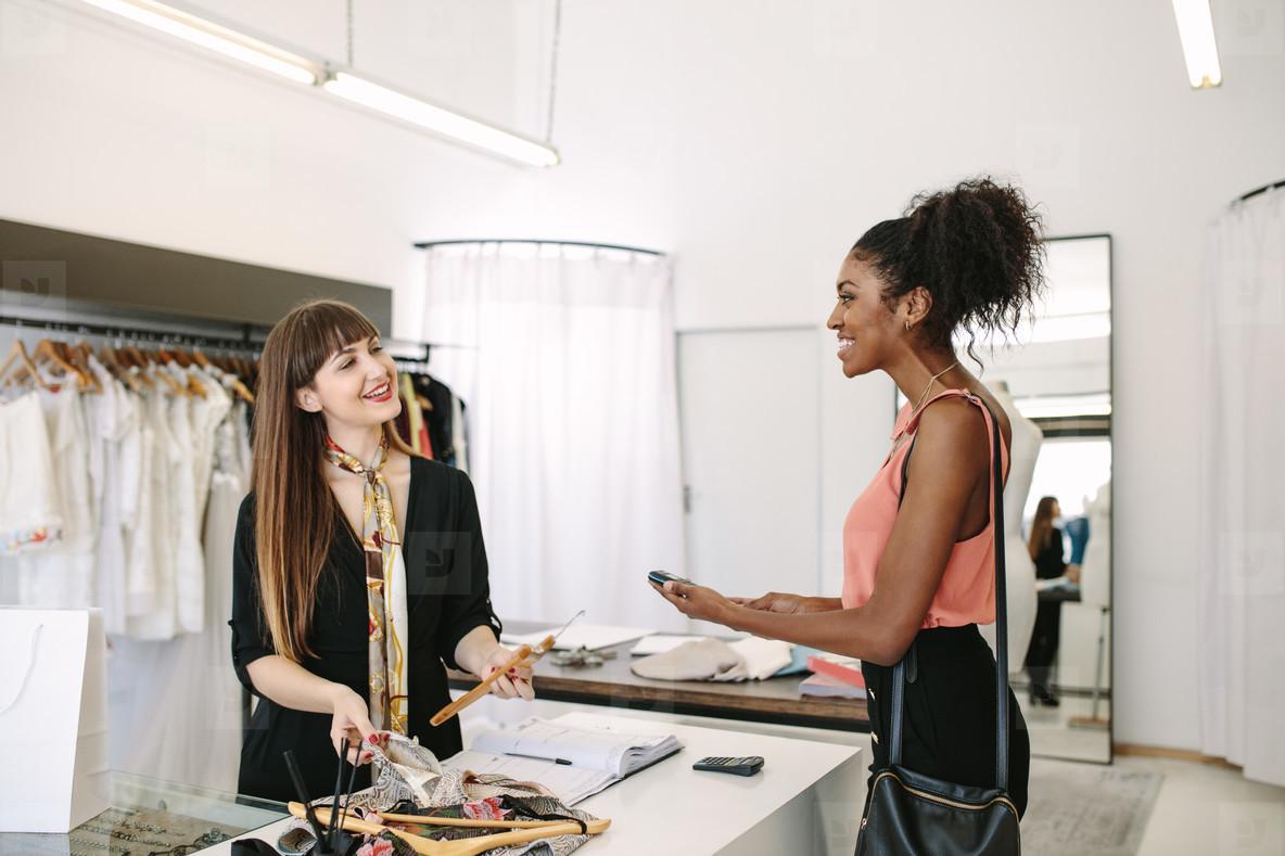 Woman entrepreneur making sale in her fashion studio