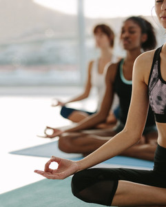 Female meditating in lotus pose at yoga class