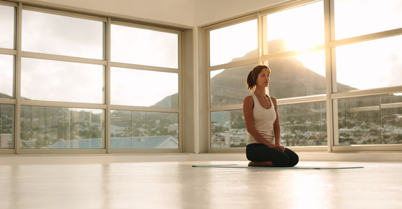 Fitness woman sitting in yoga pose at gym