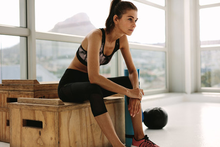 Fitness woman relaxing at gym after workout