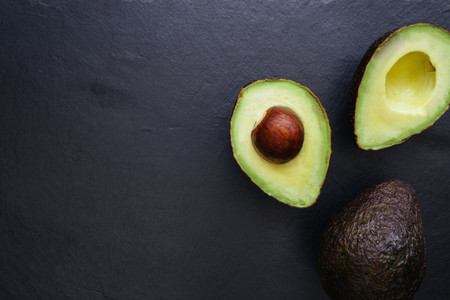 Avocado half on dark background