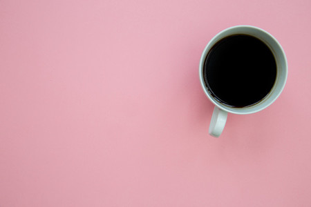 Coffee cup on bright pink background with copy space