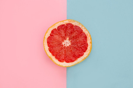 Pink grapefruit on bright pink and blue background