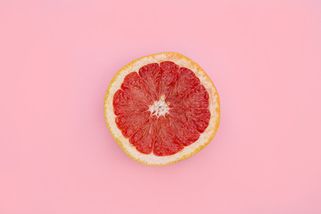Pink grapefruit half on bright pink background