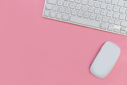 Computer keyboard and mouse on pink background