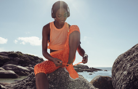 Woman tying her shoe laces before a run at beach