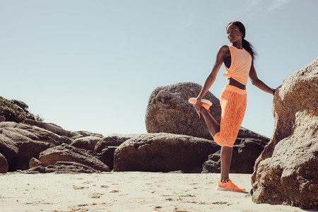African woman doing stretching workout on beach