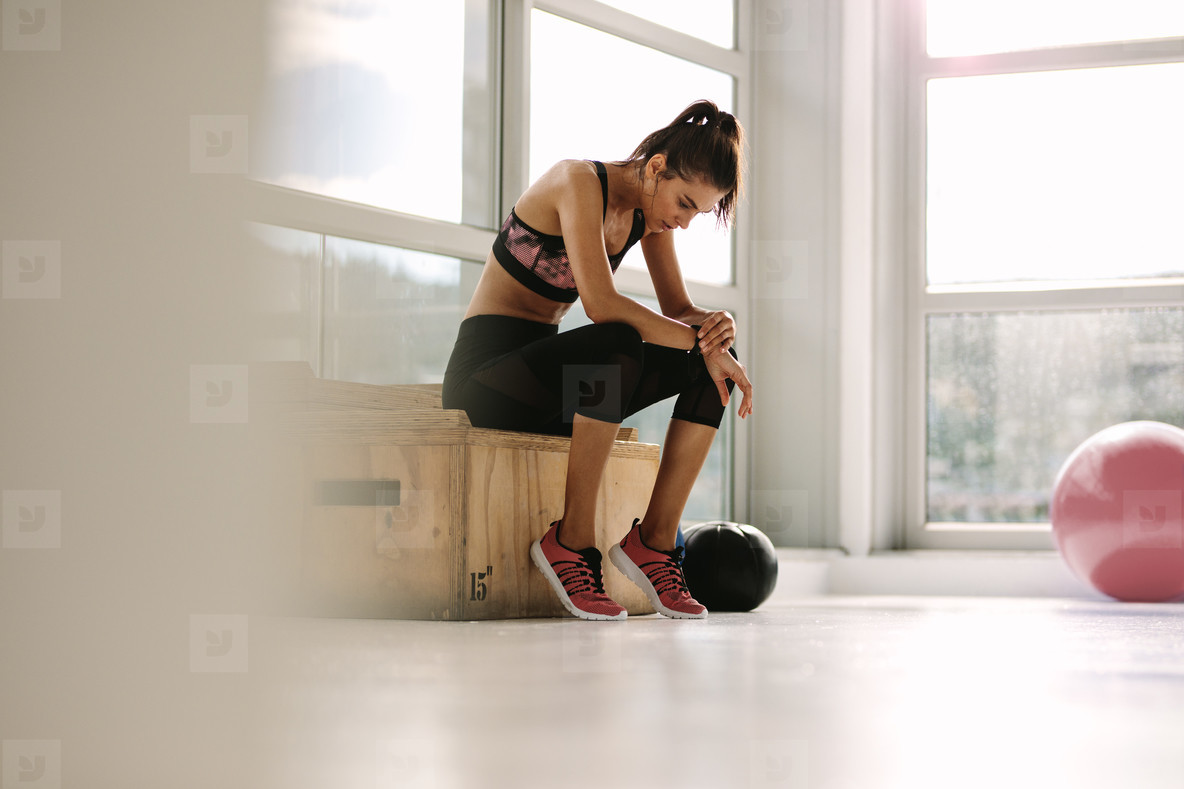 Young woman resting after workout at gym