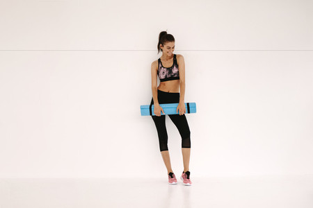 Sportswoman with yoga mat in fitness studio