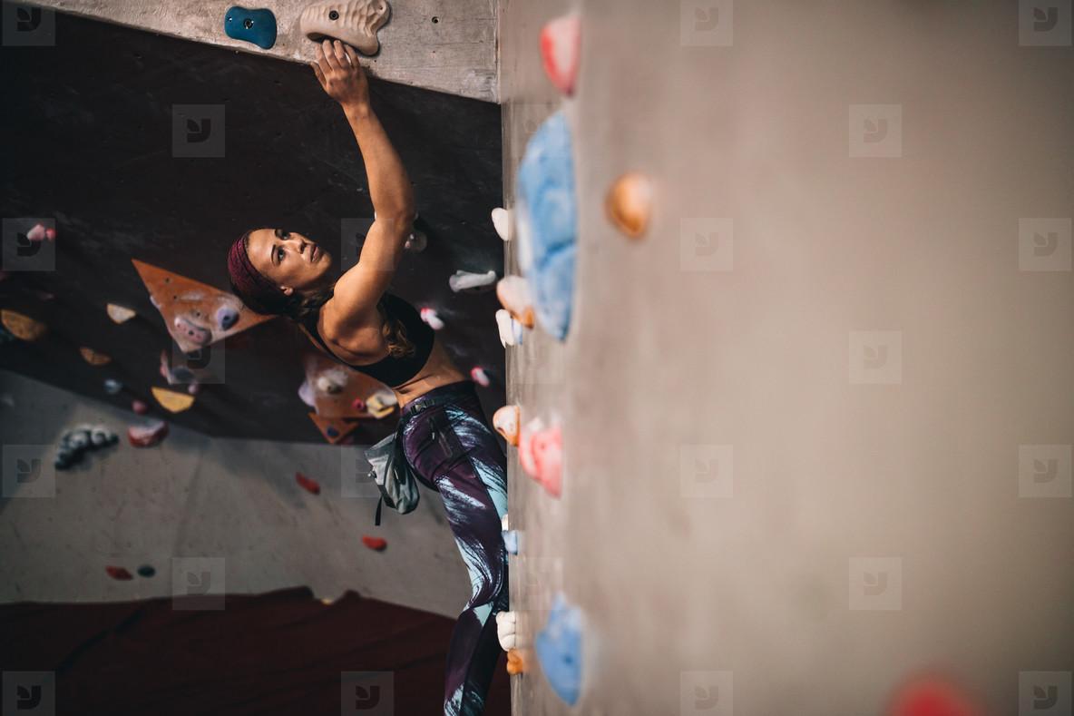 Woman climbing indoor boulder wall