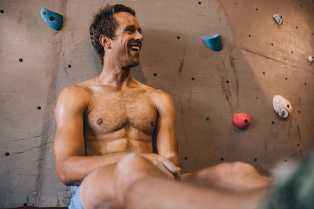 Man at a wall climbing gym taking rest