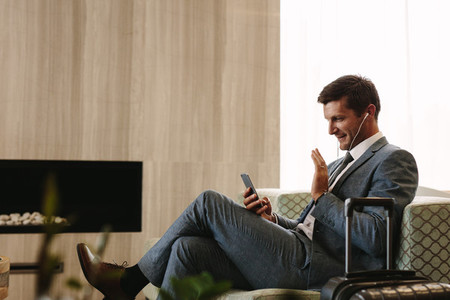 Businessman making a video call while waiting for his flight
