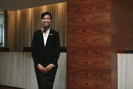 Female receptionist standing at hotel front desk