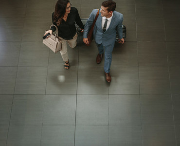 Business people walking through a hallway with luggage