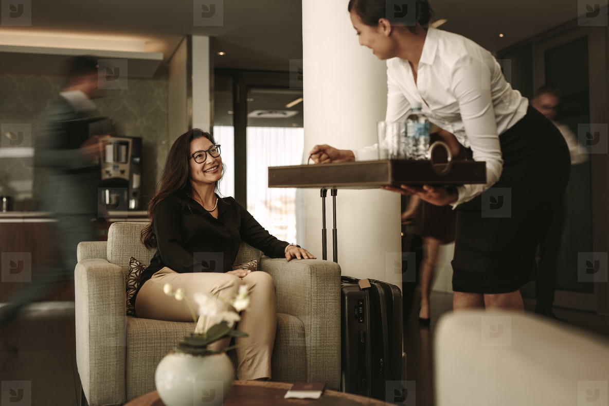 Business lounge staff serving coffee to female traveler