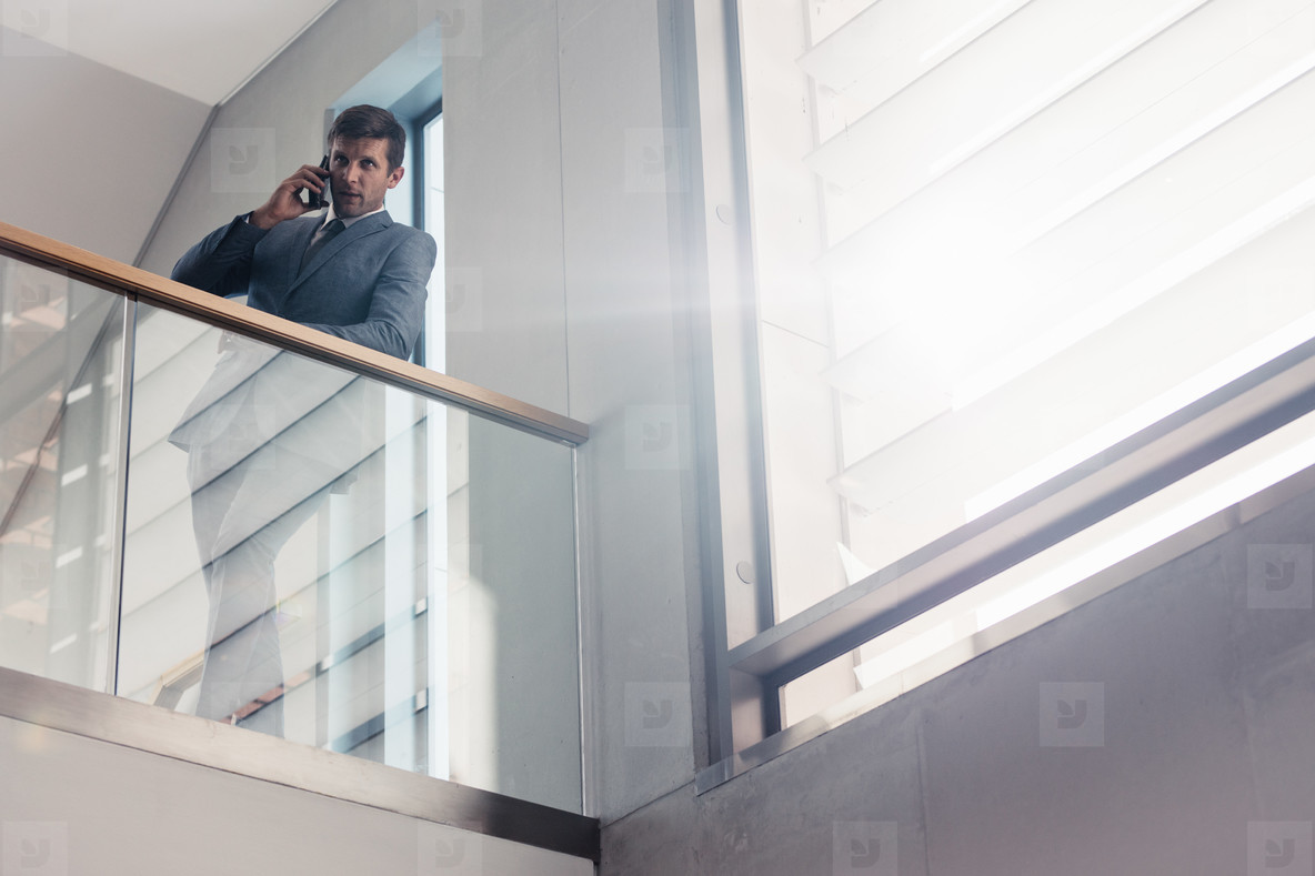 Businessman in office talking on smartphone