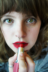 Young woman painting her lips
