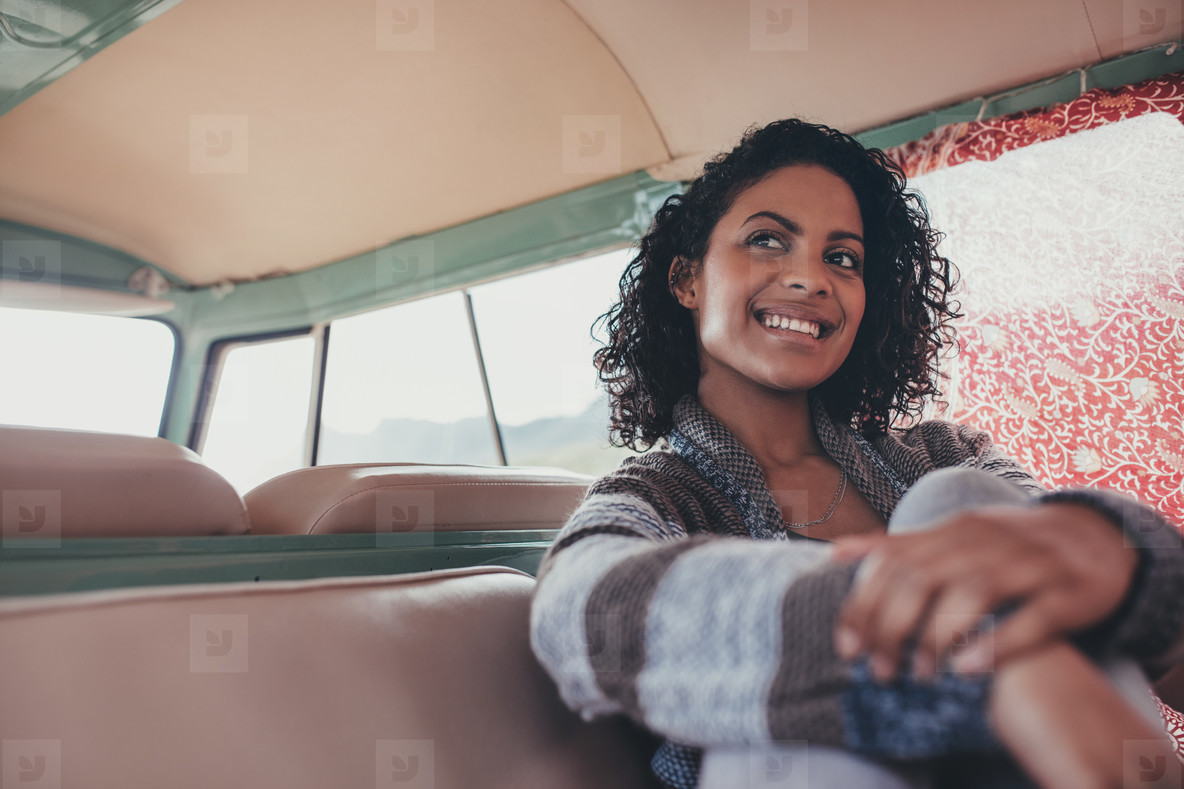 Smiling woman on roadtrip travelling by van
