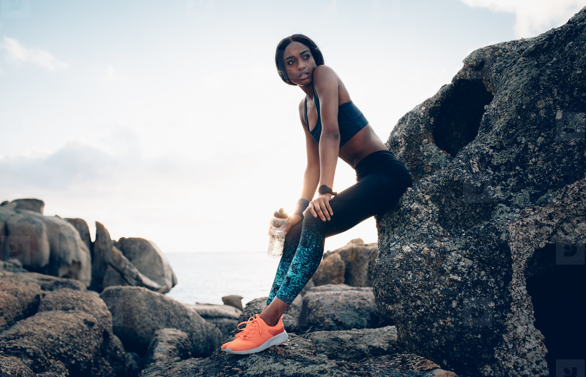 Fitness woman resting over a rock after workout