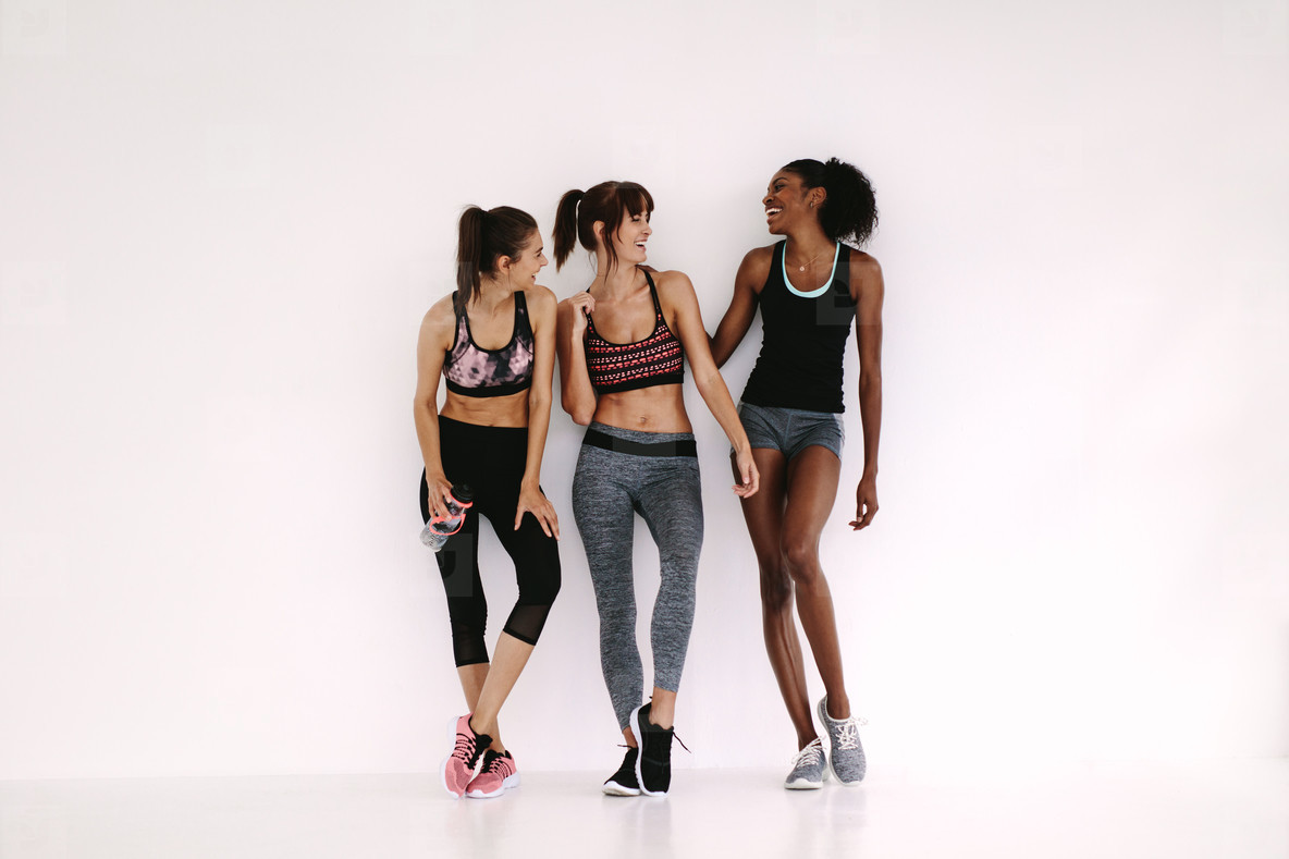 Group of sporty girls talking in fitness studio