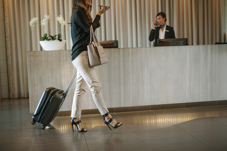 Female guest arriving in hotel with suitcase
