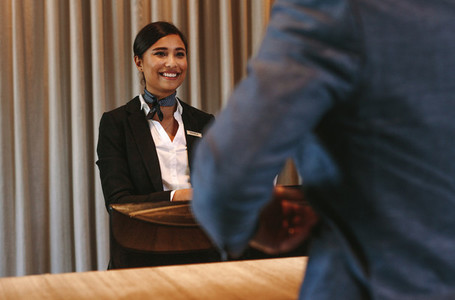 Smiling hotel receptionist attending guest at check in counter