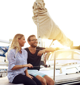 Happy Couple Sitting In front of a Sail Boat