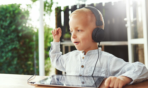 Happy little boy listening to music