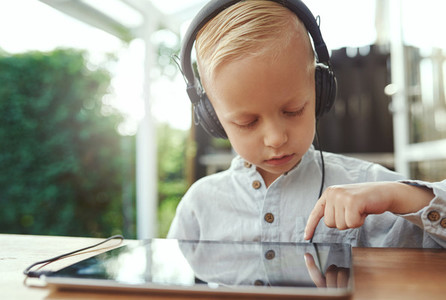 Pensive little boy selecting a new soundtrack