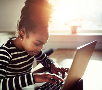 young girl typing on a laptop