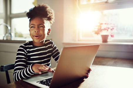 Little black girl working on a laptop computer