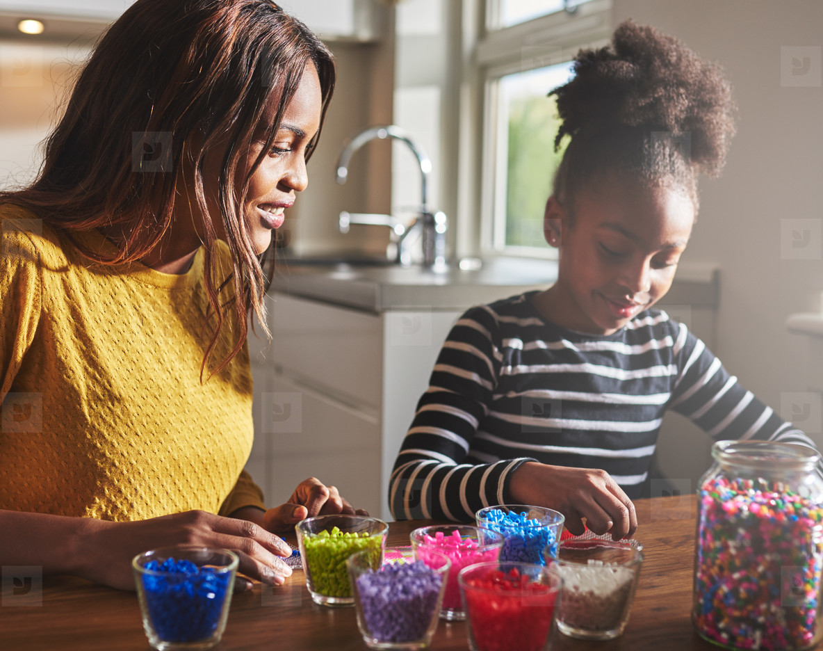 Mother and daughter creating beaded crafts