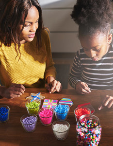 Black parent and child making beaded objects