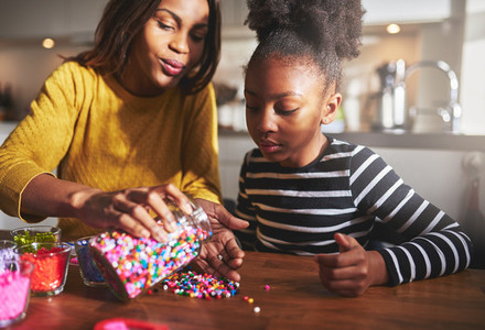 Helpful mother taking out beads for daughter