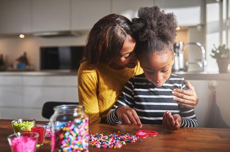 Proud parent hugging child making crafts