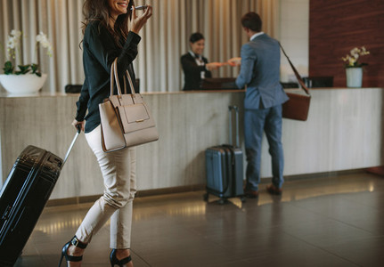 Woman arriving at hotel lobby with suitcase