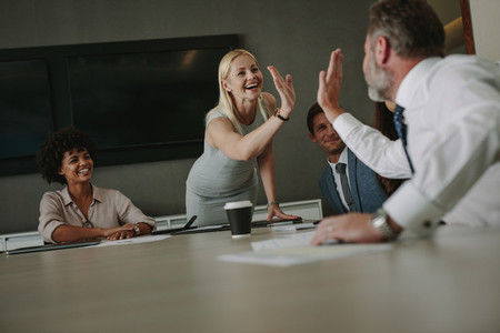 Business people giving a high five during meeting
