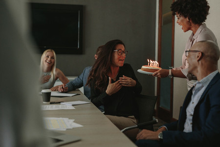 Coworkers celebrating birthday of female colleague with cake