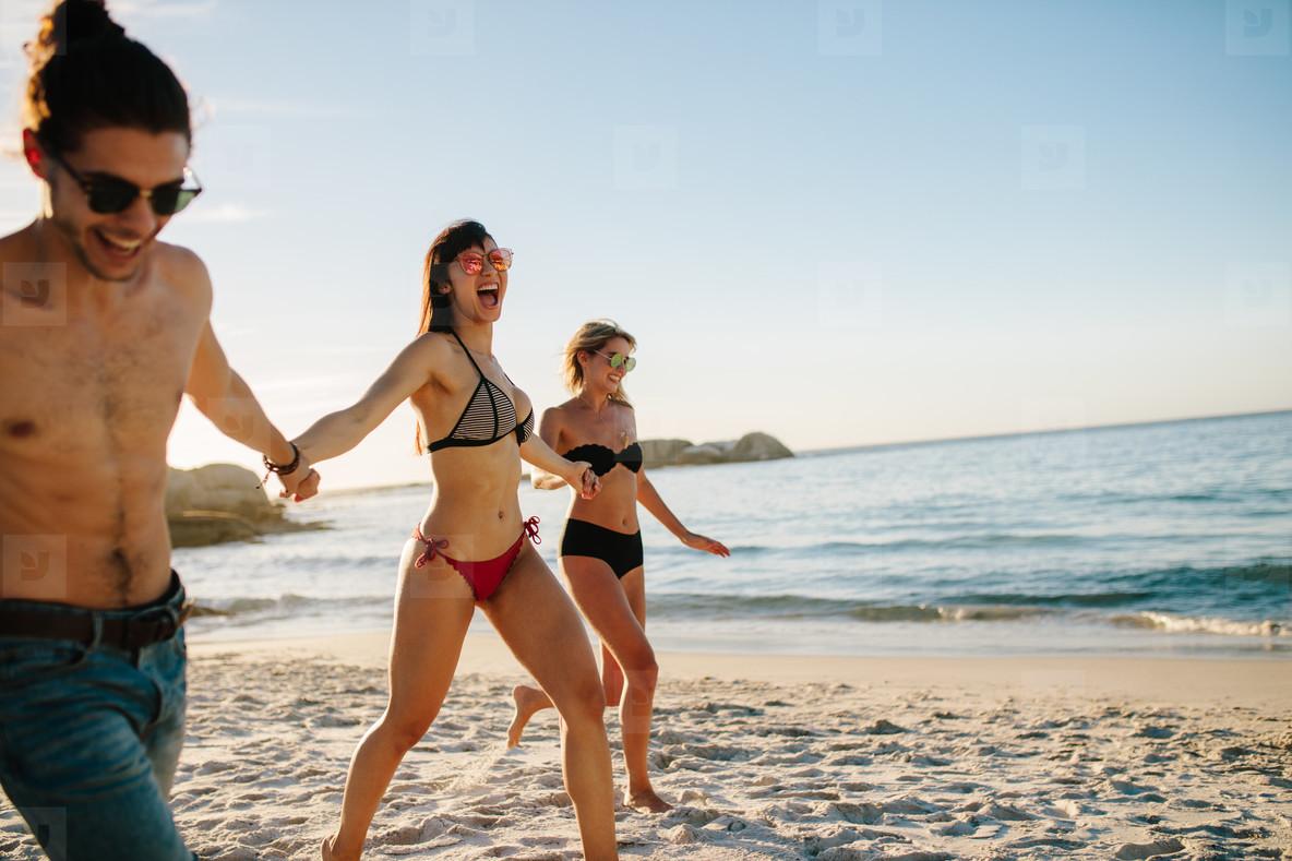 Happy friends running along the sea shore
