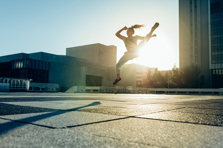 Woman practicing roundhouse kick outdoors