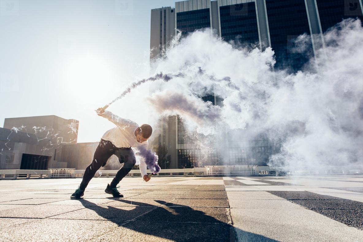Man practicing free running with smoke grenade