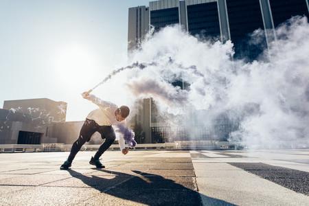 Man practicing free running with smoke grenade
