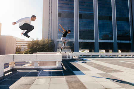 Two men doing parkour in city