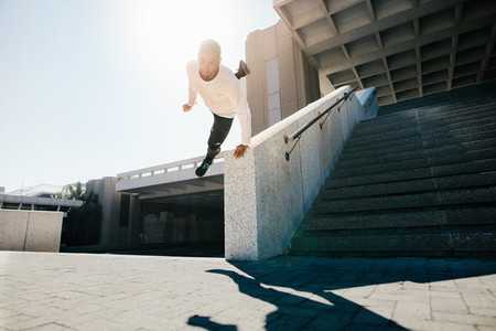 Man doing parkour wall spin in urban space