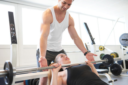 Fitness Trainer Assisting Woman Lifting Barbell
