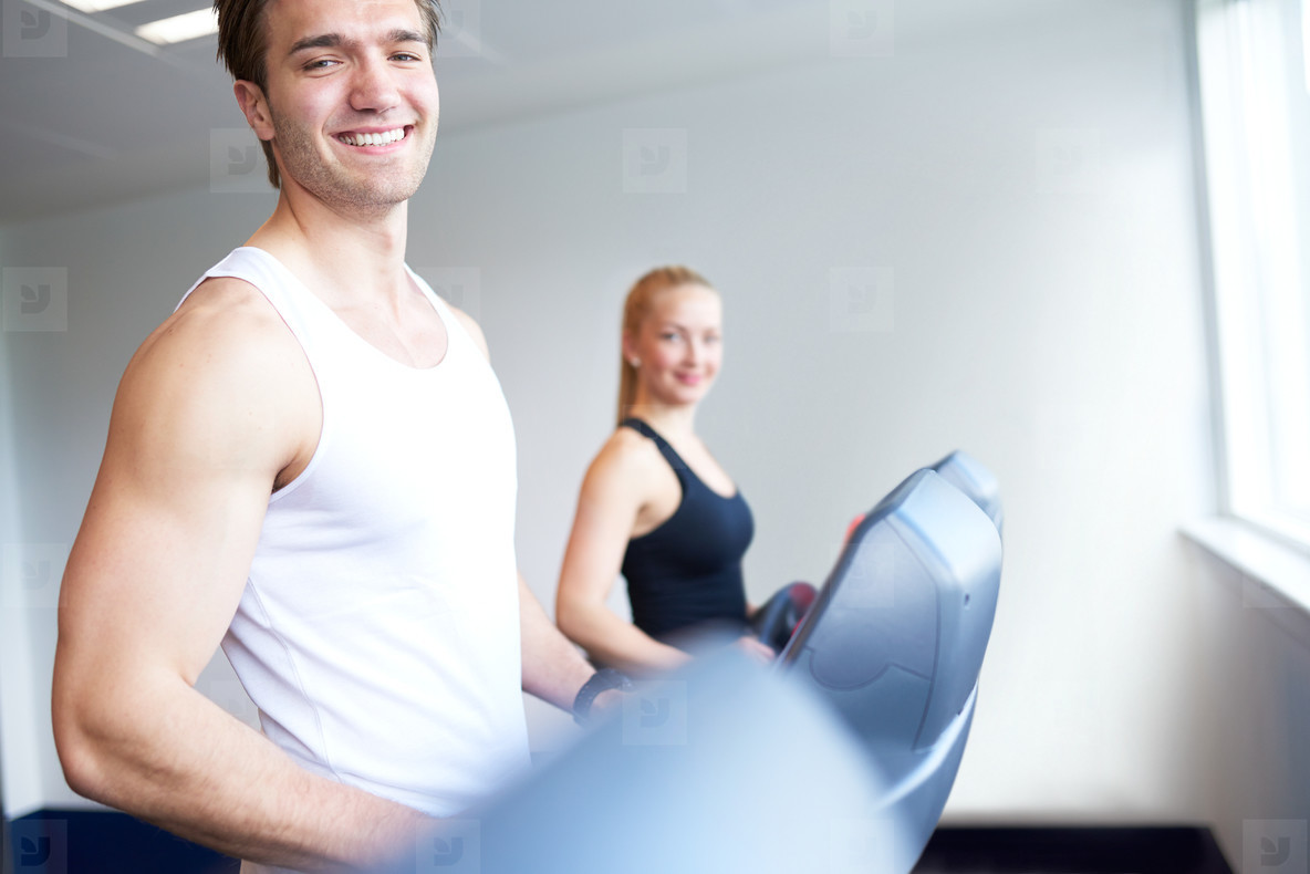 Athletic Young Man on Treadmill Smiling at Camera
