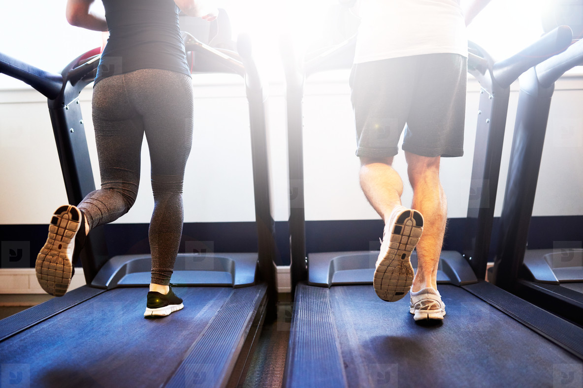 Athletic Couple Running on Treadmill Machine