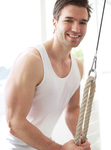 Smiling Muscular Young Guy Pulling Down Pulley