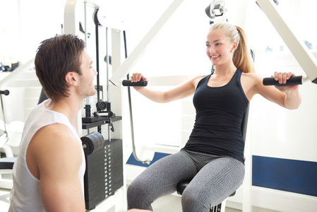 Trainer Assisting Woman on Chest Press Machine