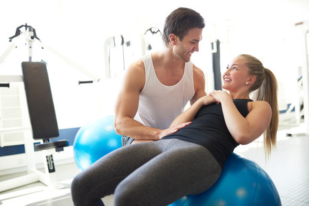 Fitness Trainer Assisting a Woman on Exercise Ball